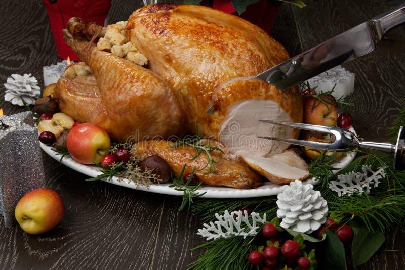 Talla de la Navidad asada Turquía con las manzanas del gancho agarrador foto de archivo libre de regalías