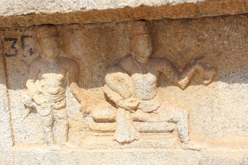 Talla de la pared del templo de Hampi Vittala del krishnadevaraya del rey con su cortesano imagenes de archivo