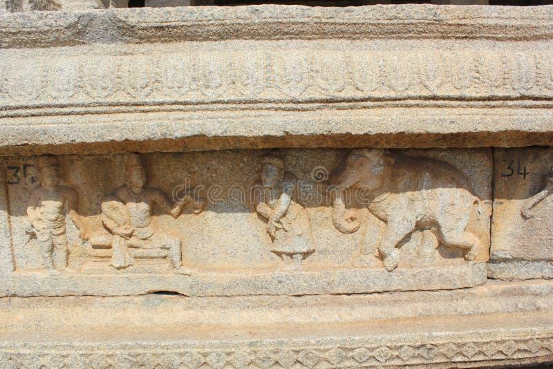 Talla de la pared del templo de Hampi Vittala del krishnadevaraya del rey y de su cortesano que hablan con un comerciante del ele fotos de archivo