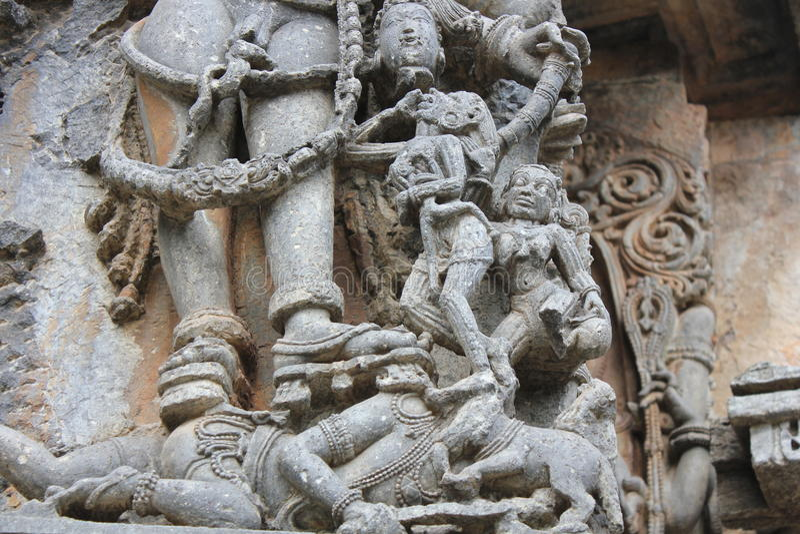 Talla de la pared del templo de Hoysaleswara de la sangre de consumición del demonio del jefe de un asura imágenes de archivo libres de regalías