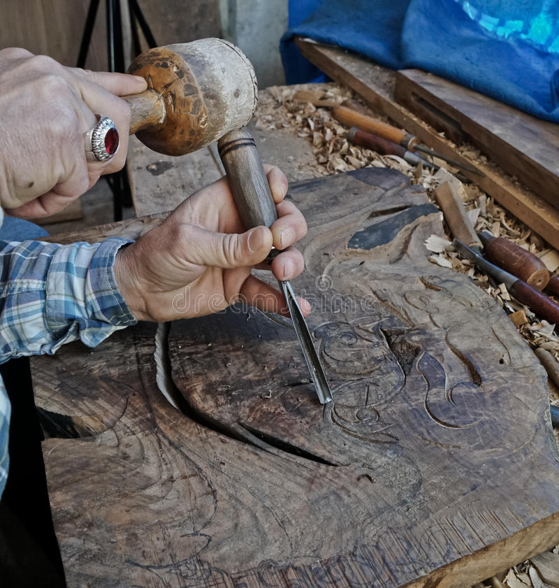 Talla de madera Carver con el cincel y el martillo fotografía de archivo libre de regalías