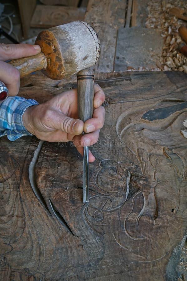 Talla de madera Carver con el cincel y el martillo fotos de archivo