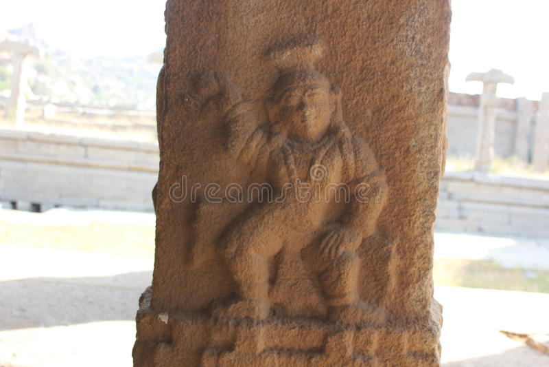 Talla del pilar de la piedra del templo de Hampi Vittala de Krishna que celebra una bola de la mantequilla foto de archivo libre de regalías