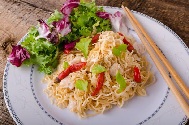Tallarines chinos con el pollo y la ensalada fresca imagenes de archivo