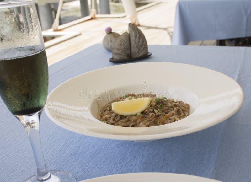 Tallarines con el limón en un restaurante vegetariano junto con un vino espumoso fotos de archivo