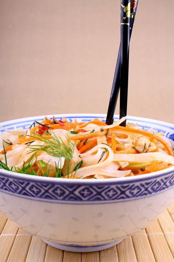 Tallarines de arroz asiáticos con la carne y los palillos del pollo foto de archivo