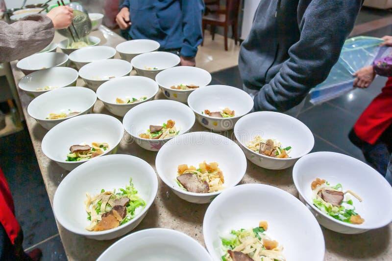 Tallarines de huevo de Yunnanese con cerdo y verduras en los cuencos blancos, comida local en Yunnan, China imagen de archivo