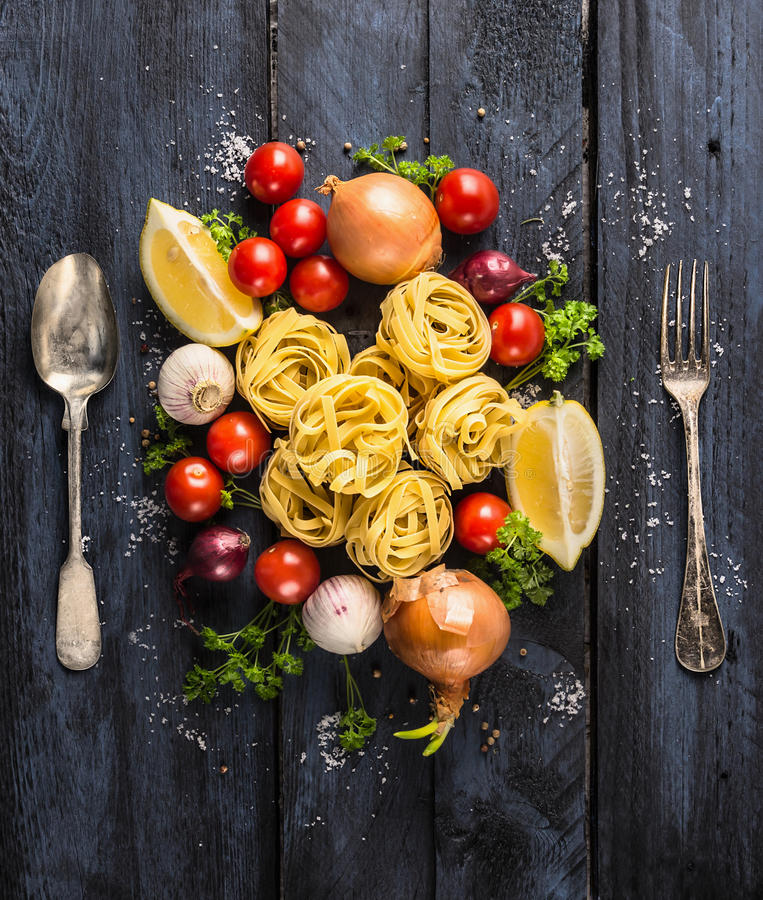 Tallarines de las pastas con los tomates, las verduras y las especias para la salsa de tomate, la cuchara y la bifurcación imagen de archivo libre de regalías