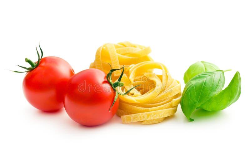 Tallarines de las pastas, tomates y hojas italianos de la albahaca foto de archivo