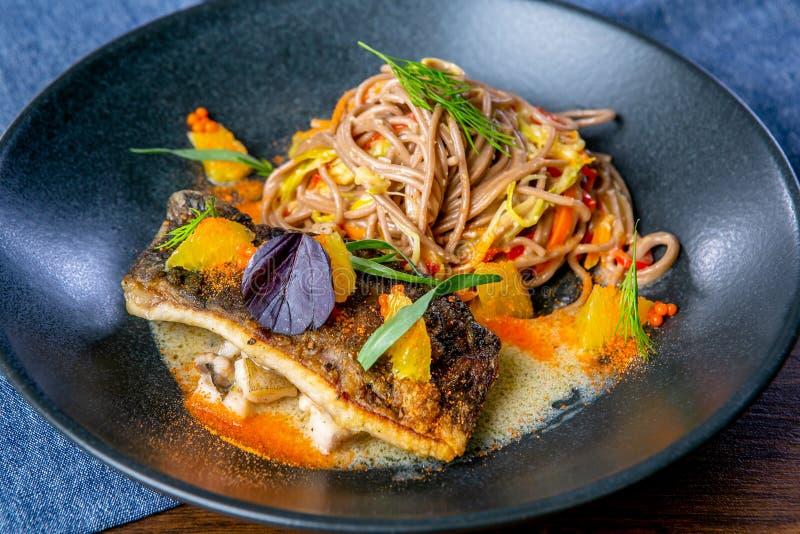 Tallarines del alforfón en el wok y la carpa cocida Cocina asiática El trabajo de un cocinero profesional Plato de un menú del re imágenes de archivo libres de regalías