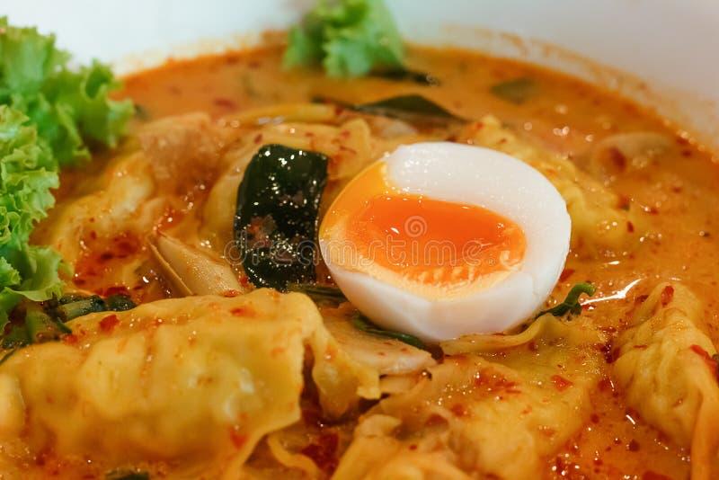 Tallarines en la sopa picante tailandesa de tom yum con Wonton del huevo y del camarón fotos de archivo libres de regalías