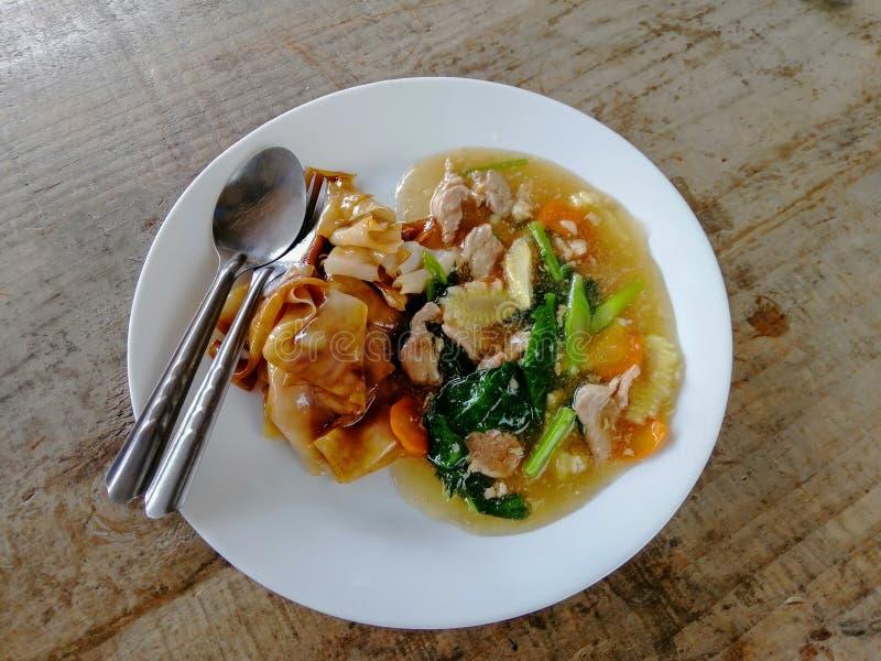 Tallarines fritos con el cerdo, la col rizada china y la llamada tailandesa Rad Na de la zanahoria en la placa blanca imágenes de archivo libres de regalías
