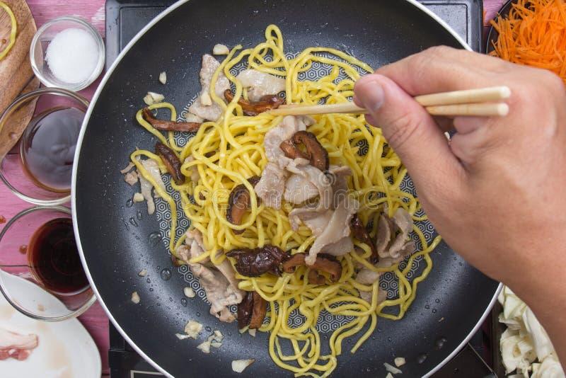 Tallarines sofritos cocinero de Yakisoba en cacerola imagen de archivo