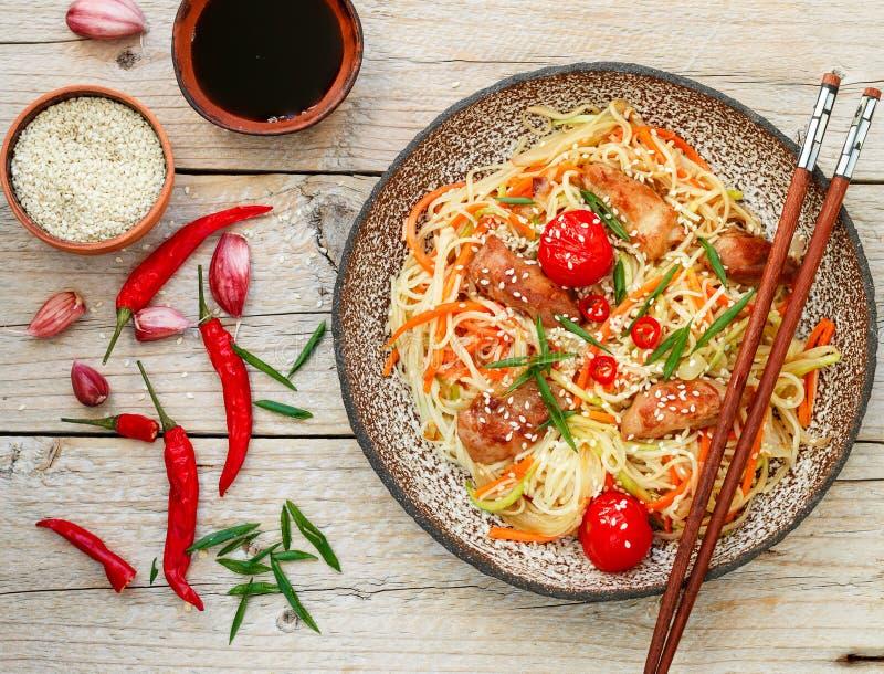 Tallarines sofritos con el pollo, la verdura, las semillas de sésamo y la salsa de soja foto de archivo
