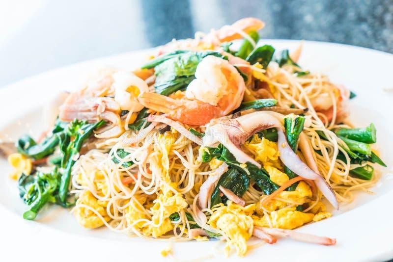 Tallarines sofritos con los mariscos y las verduras mezcladas imagen de archivo