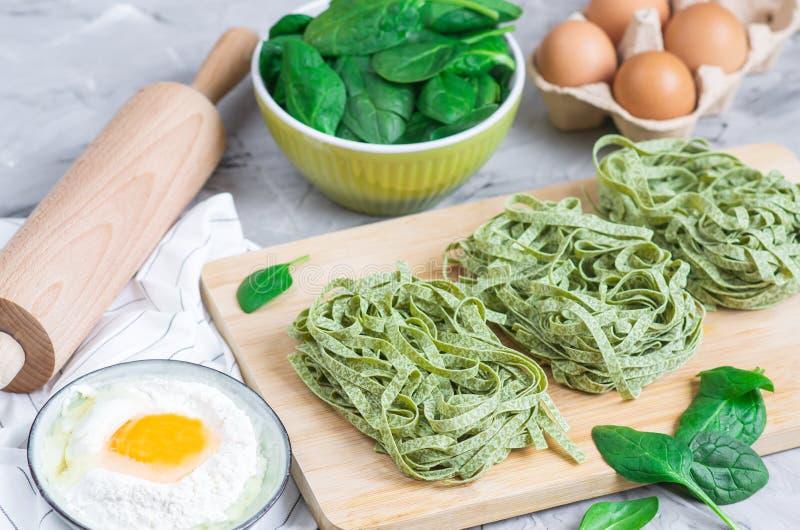 Tallarines verdes hechos en casa crudos italianos de las pastas de la espinaca de la preparación que cocinan ingredientes de la t foto de archivo libre de regalías
