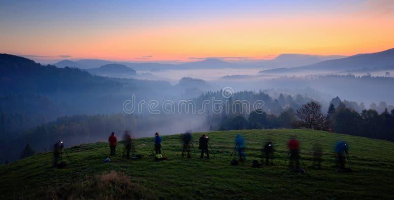 Taller de la fotografía del paisaje Fotógrafos en curso durante salida del sol de la montaña Colinas y pueblos con mañana de nieb fotografía de archivo