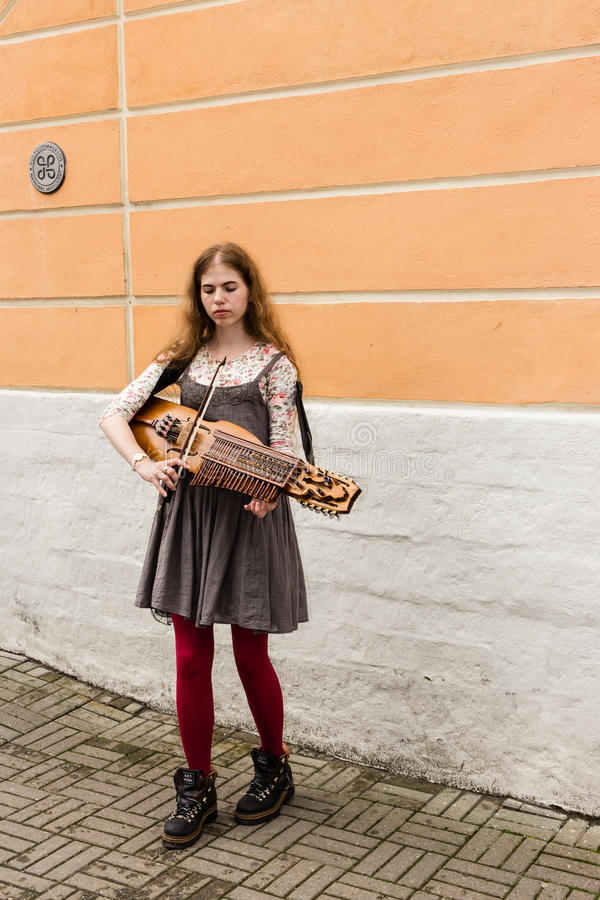 TALLIN, ESTLAND - CIRCA 2016: Een vrouwelijke straatmusicus speelt nyckelharpa op een zijgang in de oude stad van Tallin in Estla stock foto