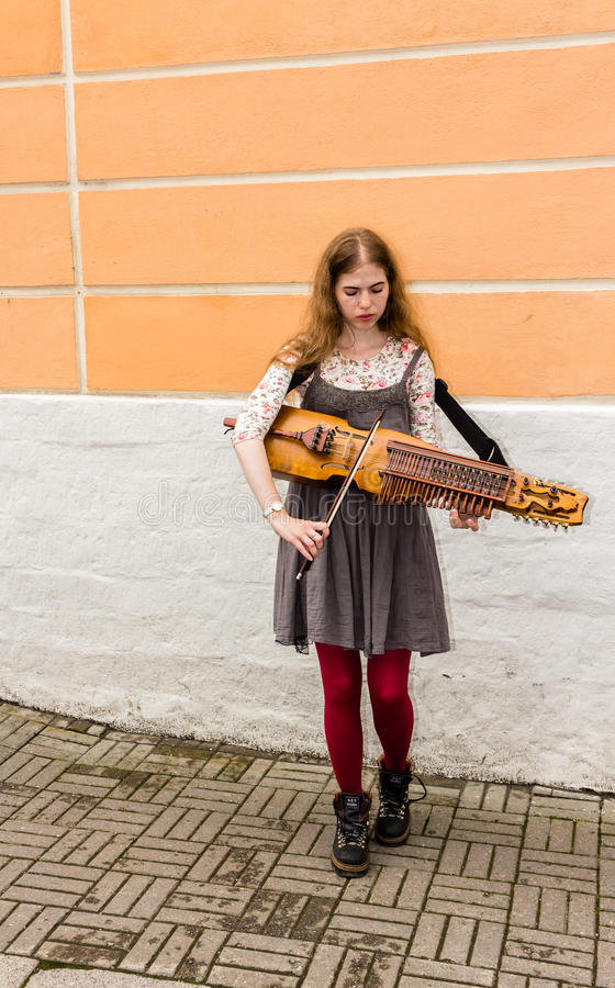 Free TALLIN, ESTONIA - CIRCA 2016: A Female Street Musician Plays The Nyckelharpa On A Side Walk In The Old Town Of Tallin In Estonia. Stock Photography - 93216532