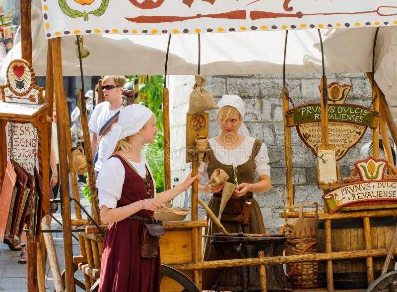 TALLINN ESTLAND - JULI 8, 2006: Turister i gammal stad Säljare av mandelmuttrar i medeltida klänningar arkivfoto