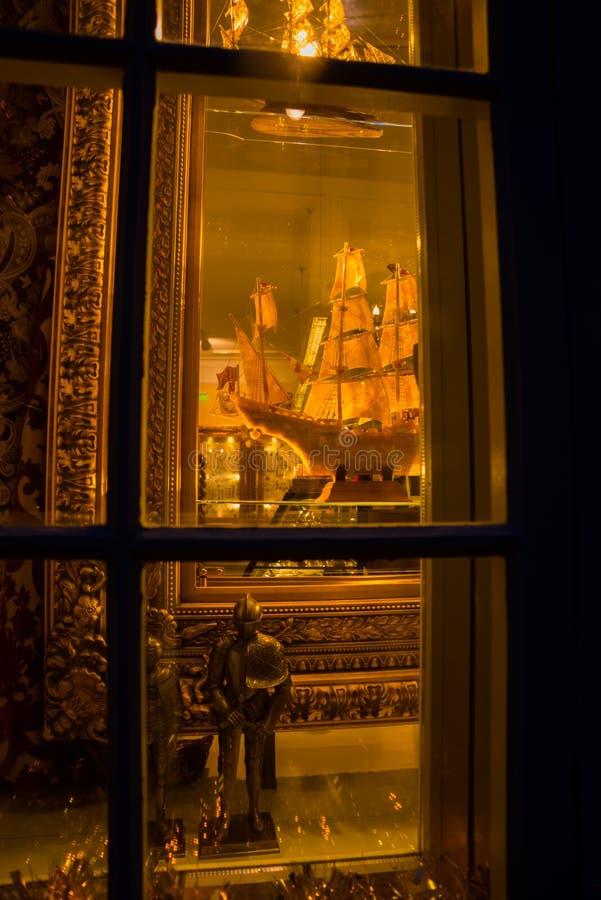 Tallinn Estland: Statyer av guld- medeltida riddare och skeppet med master i souvenir shoppar royaltyfri foto
