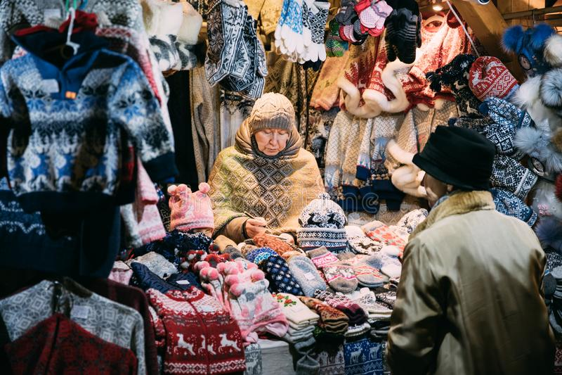 Tallinn, Estonia. Woman Seller Sells Various Colorful Knitted Traditional European Warm Clothes - Caps Hats And Mittens royalty free stock photography