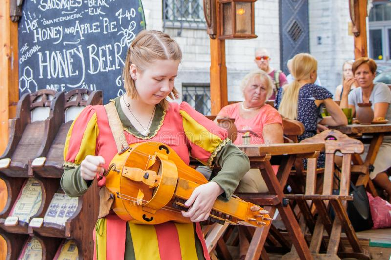 On the street of the old town of Tallinn girl in a national costume adjusts folk instrument royalty free stock image