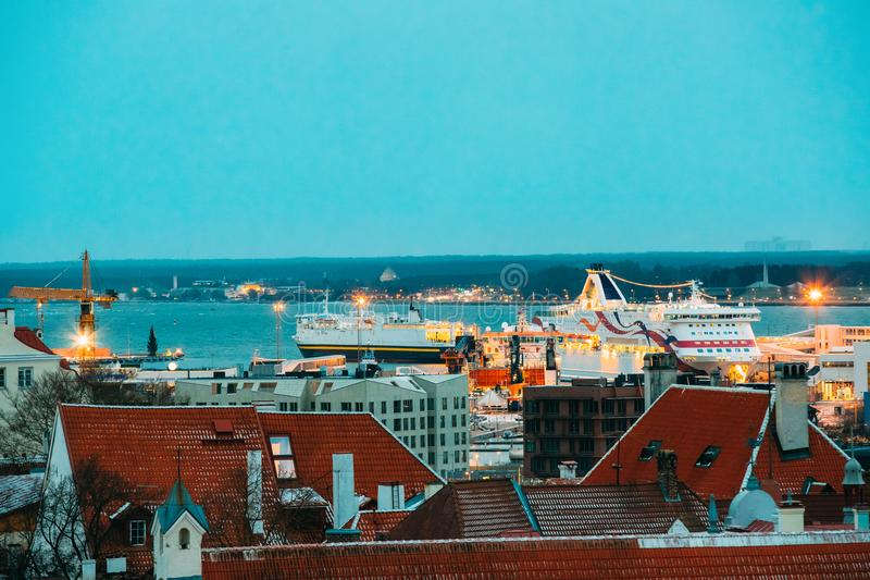 Tallinn, Estonia. Modern Ferry Ferryboat At Pier Awaiting Loading. Cargo From Port And Passenger Boarding From Terminal. View From Old Town In Evening Or Night stock image