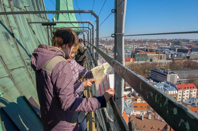 Tallinn, Estonia, 02 puede 2017 Los turistas ven el mapa en la plataforma de observación de la iglesia de Oleviste imagen de archivo libre de regalías