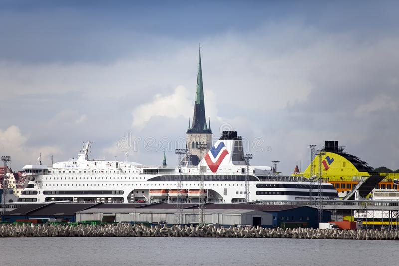 TALLINN, ESTONIA- SEPTEMBER 7, 2015: The big cruise ship in port and a spike of ancient church royalty free stock photo