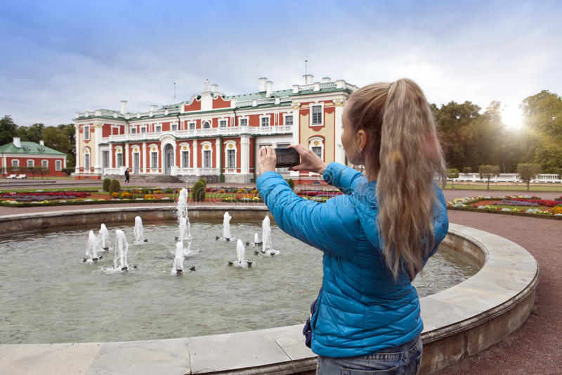 TALLINN, ESTONIA- SEPTEMBER 7, 2015: The woman photographs the Kardiorg palace at Kadriorg Park on phone in Tallinn, Estonia royalty free stock image
