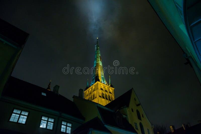 Tallinn, Estonie : Église de St Olaf La flèche d'église est illuminée Vue inférieure Vieille ville avec des maisons la nuit photo stock