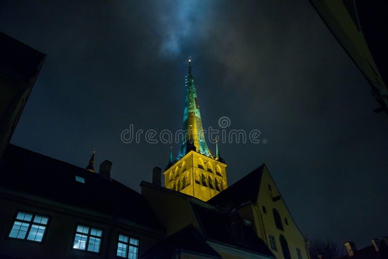 Tallinn, Estonie : Église de St Olaf La flèche d'église est illuminée Vue inférieure Vieille ville avec des maisons la nuit photographie stock libre de droits
