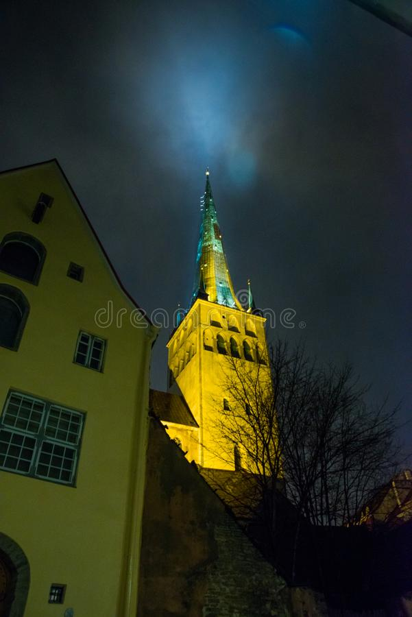 Tallinn, Estonie : Église de St Olaf La flèche d'église est illuminée Vue inférieure Vieille ville avec des maisons la nuit photo libre de droits