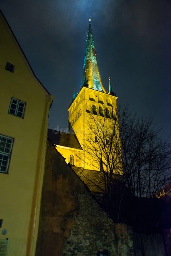 Tallinn, Estonie : Église de St Olaf La flèche d'église est illuminée Vue inférieure Vieille ville avec des maisons la nuit photos stock
