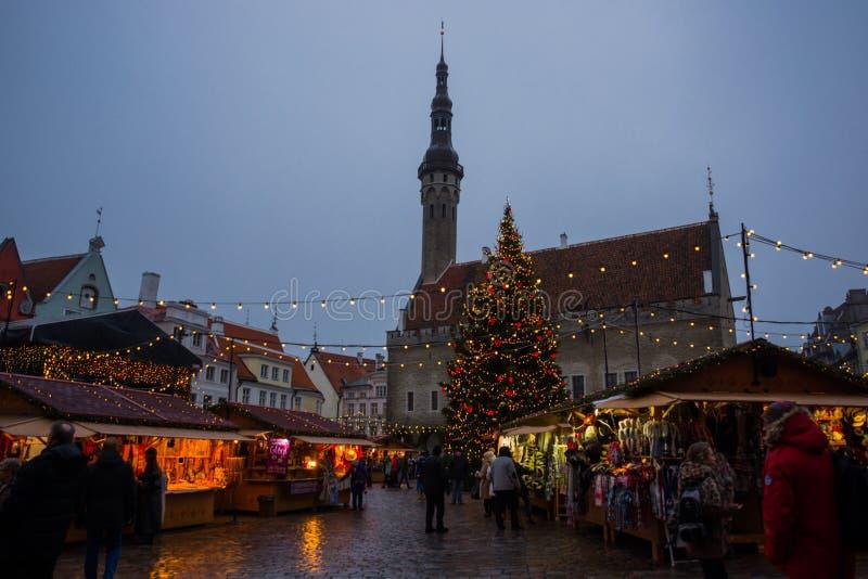 TALLINN, ESTONIE : Les gens apprécient le marché de Noël du paysage de nuit de Tallinn avec le bâtiment de Hall Tower avec l'arbr photographie stock libre de droits