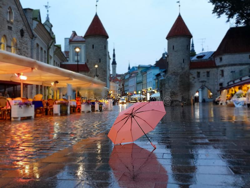 Tallinn  Old Town night   city light  pink umbrella  rainy season street evening lightening  blurring bokeh city  people walking. Autumn leaves fall sidewalk royalty free stock photo