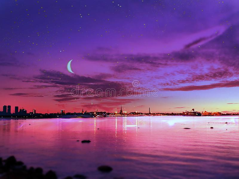 Sunset at sea sun light sky line evening light reflection on sea water gold summer sunset city panorama on horizon  Old town Talli. Tallinn old town night moon royalty free stock photo