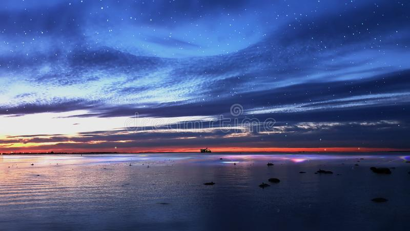Sunset at sea sun light sky line evening light reflection on sea water gold summer sunset city panorama on horizon  Old town Talli. Tallinn old town night moon stock photo