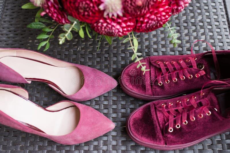 Talones de la boda CONTRA las zapatillas de deporte nupciales Accesorios nupciales de la boda roja: talones y zapatillas de depor foto de archivo