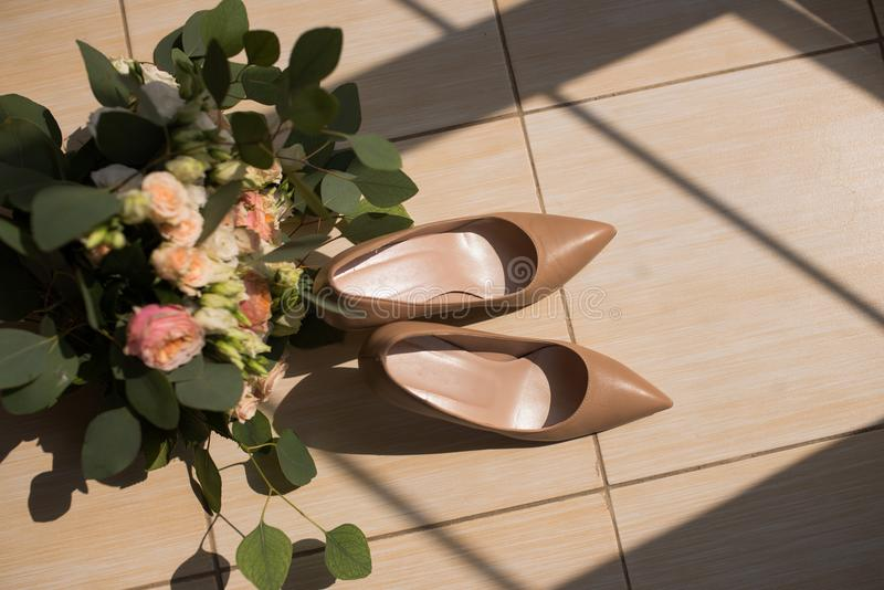 Talons hauts beiges de mariage nuptiale à la mode sur le plancher beige photographie stock