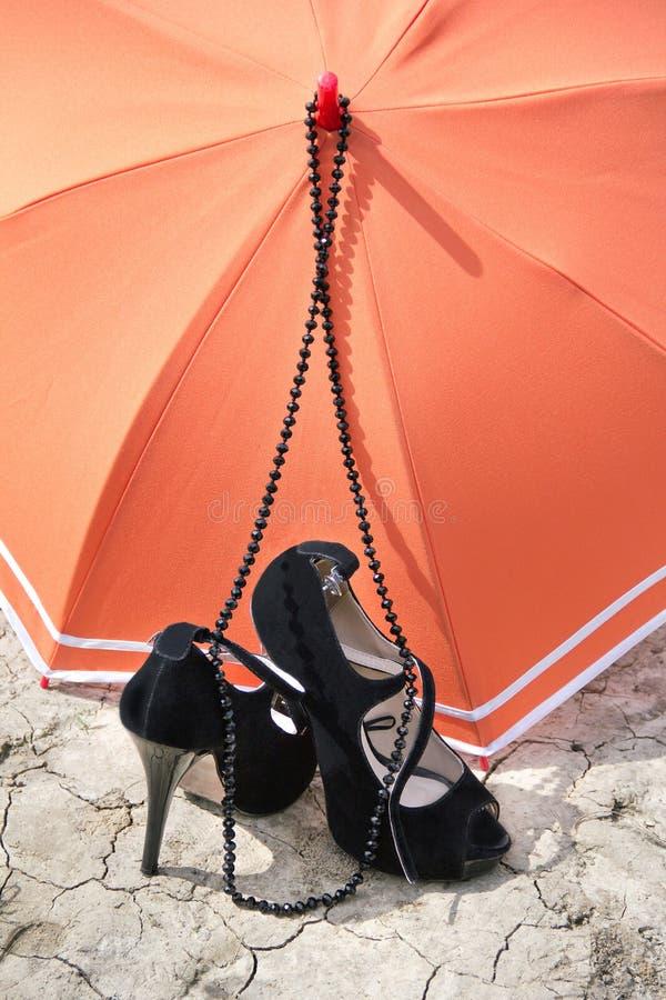 Talons stylets, collier et parapluie sur une terre criquée images libres de droits