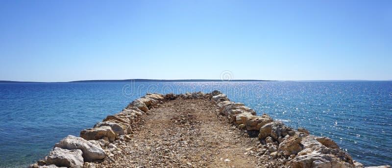Talpa delle pietre diritto in un mare cristallino sotto il cielo blu immagini stock libere da diritti
