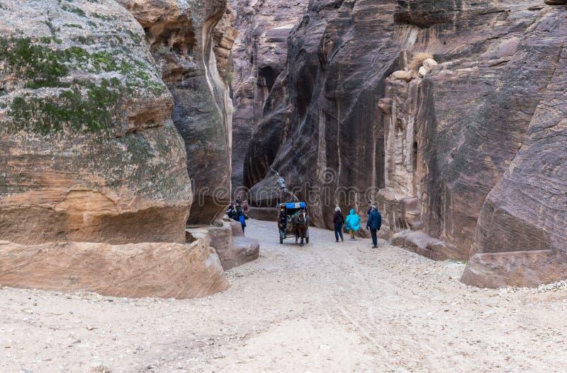 Talrijke toeristen onderzoeken en fotograferen de bergen de plaats bepaalden van dichtbij de weg die tot Petra leiden - het kapit stock fotografie