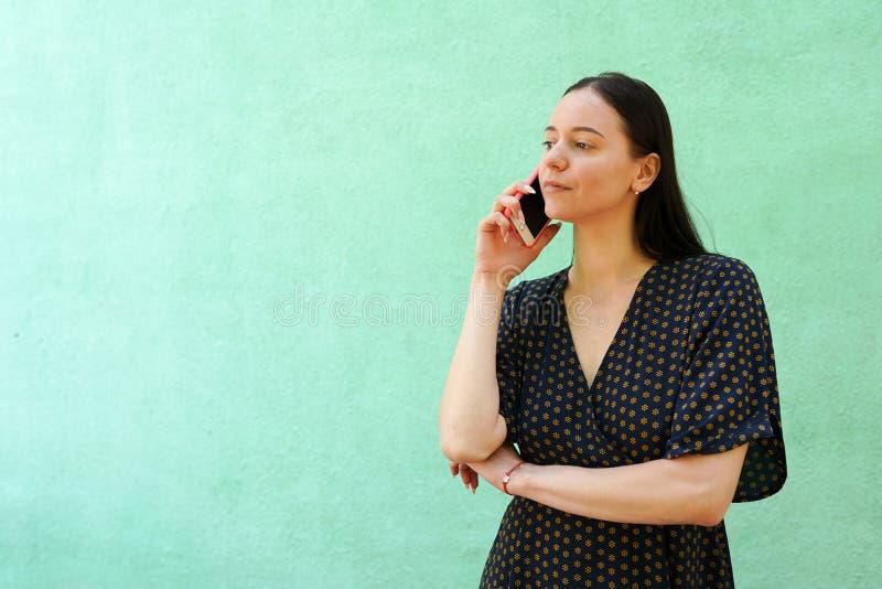 taltking在绿色背景的电话的美丽的年轻女人画象与拷贝空间 免版税库存图片