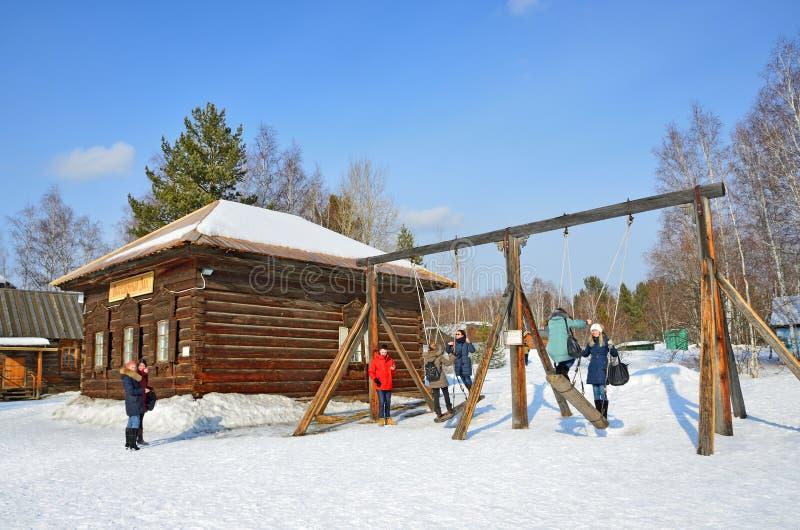 Taltsy, het gebied van Irkoetsk, Rusland, 02 Maart, 2017 Mensen die op oude Russische schommeling in het architecturaal-etnografi royalty-vrije stock afbeelding