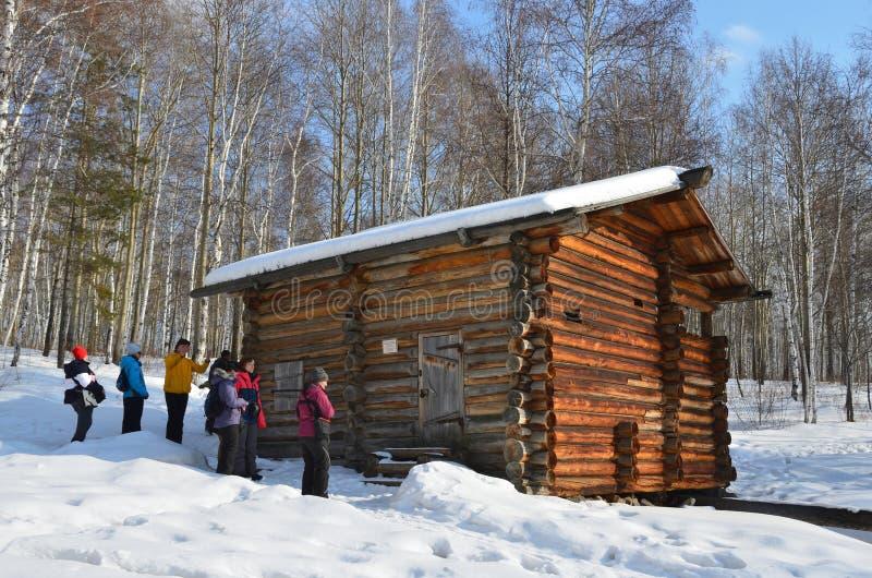 Taltsy, región de Irkutsk, Rusia, marzo, 02, 2017 Turistas que visitan la cascada de los molinos de agua líquidos del pueblo de V foto de archivo libre de regalías