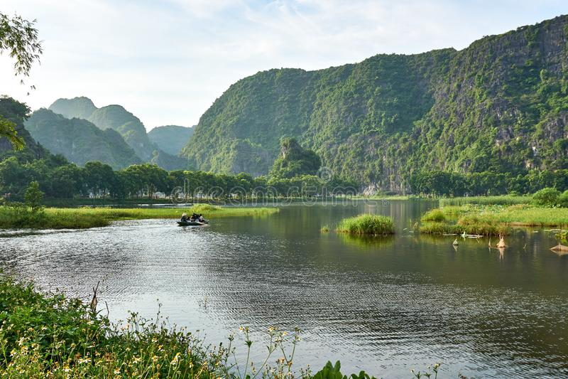 Tam Coc, Vietnam - 8 de junio de 2019: Viaje turístico del barco que toma a través del coc del tam Paisaje con las montañas y el  fotos de archivo libres de regalías