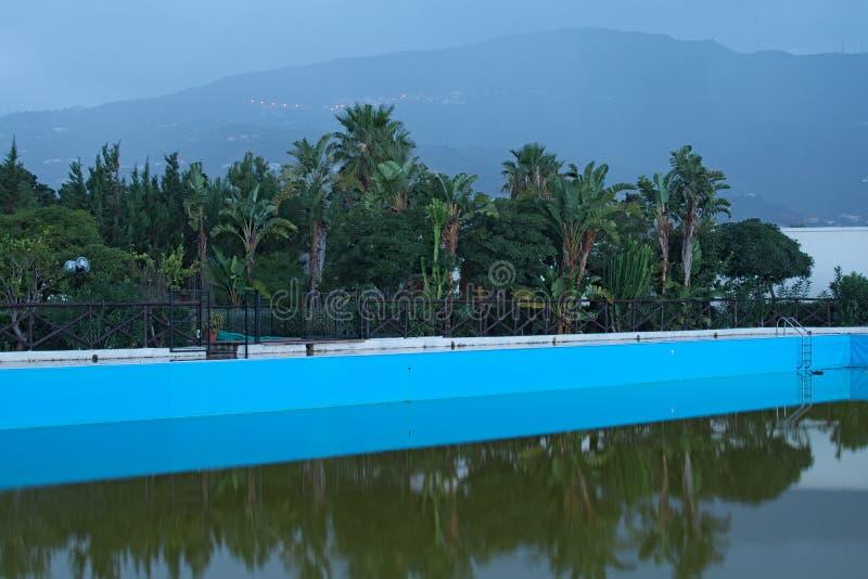Tam jest mały park z różni drzewa za basenem W tło górach w mgle Marina Di Patti sicily zdjęcia stock