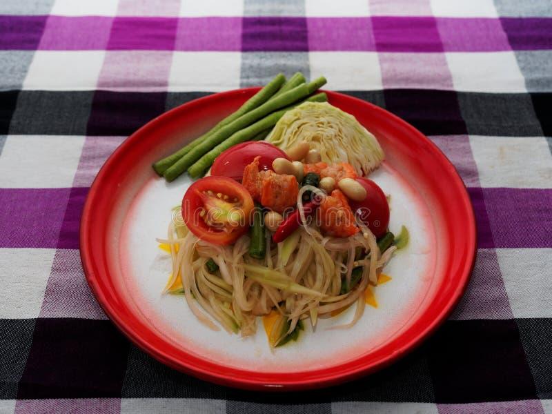 Tam verde tailandese del som dell'insalata della papaia in vassoio tradizionale della stampa floreale sul fondo tailandese porpor fotografie stock